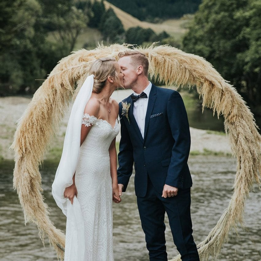 Feature-Jess-Daisy-Aster-wedding-dress-couple-kissing-wreath